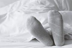 Chaussettes grises détendant sur le lit blanc photos libres de droits