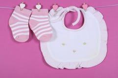 Chaussettes mignonnes et bavoir roses de crèche de bébé et blancs de rayure Images stock