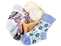 Chaussettes, panier et boules tricotés de fil avec des aiguilles Image stock
