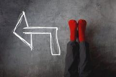 Chaussettes rouges et flèche indiquant la gauche Photographie stock libre de droits