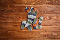 Chaussettes tricotées multicolores rayées de bébé sur un fond en bois photos stock