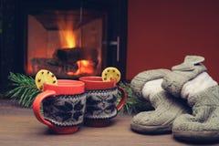 Chaussettes tricotées près de la cheminée avec la tasse de thé chaud sur la vieille table Images libres de droits