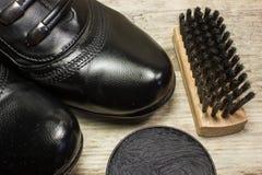 Chaussez la brosse, le cirage à chaussures et les chaussures noires Image stock
