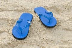 Chausson bleu sur une plage sablonneuse Photographie stock libre de droits