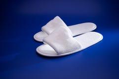 Chaussons blancs sur le fond bleu Photographie stock
