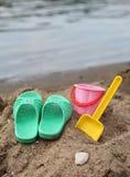 Chaussons et jouets d'enfants sur la plage Photo libre de droits