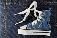 Chaussure bleue minuscule sur le fond de denim Photographie stock