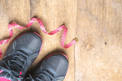 Chaussure d'espadrille de sports avec la bande de mesure sur le fond en bois Images libres de droits