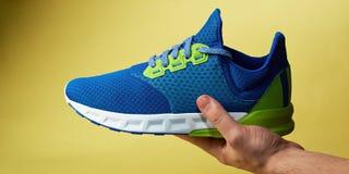 Chaussure de sport étendue en main Photos stock