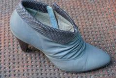 chaussure en cuir grise avec un talon sur une table brune photo libre de droits