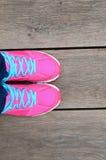 Chaussure rose de sport sur le plancher en bois de lamelle Photos stock