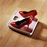 Chaussure rouge de talon sur l'échelle rose de poids Photographie stock