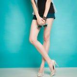 Chaussures à la mode de talons hauts argentés sur les jambes femelles sexy Photographie stock libre de droits