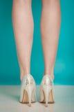 Chaussures à la mode de talons hauts argentés sur les jambes femelles sexy Photos stock