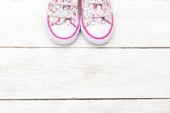 Chaussures à la mode pour de petites filles sur le fond en bois blanc Image libre de droits