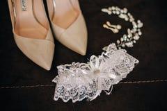 Chaussures à talons hauts avec l'ornement et le bandage de cheveux de boucles d'oreille pour le ` s de jeune mariée Photo stock