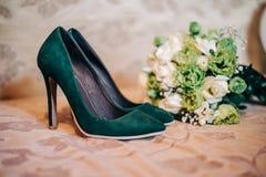 Chaussures à talons hauts de beau vert de mariage pour la jeune mariée avec un bouquet luxuriant Photo libre de droits