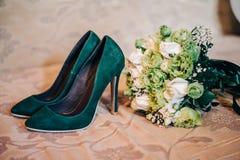 Chaussures à talons hauts vertes avec le bouquet nuptiale Photographie stock libre de droits