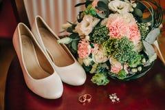 Chaussures élégantes de jeune mariée avec le bouquet des fleurs Image libre de droits