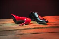 Chaussures élégantes rouges et noires sur le plancher en bois la nuit Photographie stock libre de droits