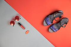 Chaussures, accessoires et cosmétiques du ` s de femmes sur le rouge et bleu-gre photographie stock