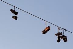 Chaussures balançant sur un câble électrique au-dessus de la rue Photographie stock