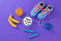 Chaussures, banane, verre d'eau, corde à sauter et petit déjeuner Photographie stock