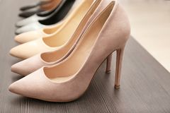 Chaussures beiges élégantes sur l'étagère en bois, Photographie stock libre de droits