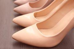 Chaussures beiges élégantes sur l'étagère en bois, Image stock