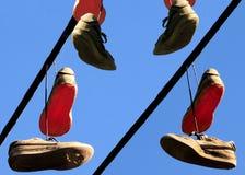 Chaussures bien usées de sport pendant de la ligne électrique Photo libre de droits
