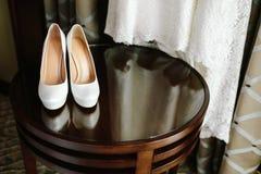 Chaussures blanches élégantes de luxe de mariage sur la table en bois avec une robe à l'arrière-plan Photos libres de droits
