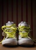 Chaussures blanches avec des dentelles de chaux et chaussettes sur le fond rayé Image stock