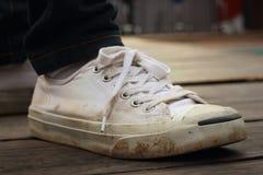 Chaussures blanches avec des jeans sur le fond du ciment Photos stock