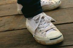 Chaussures blanches avec des jeans sur le fond du ciment Photographie stock