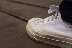 Chaussures blanches avec des jeans sur le fond du ciment Image libre de droits