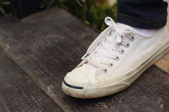 Chaussures blanches avec des jeans sur un fond noir Photographie stock