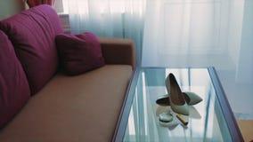 Chaussures blanches de jeunes mariées à la table en verre banque de vidéos