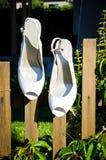 Chaussures blanches de mariage accrochant sur la barrière Photographie stock libre de droits