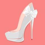 Chaussures blanches de mariage avec des talons hauts avec un arc sur un rose Photographie stock libre de droits