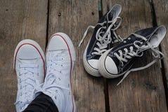 Chaussures blanches de port d'adolescent se reposant à côté des ricanements noirs, concept bien choisi Photo stock