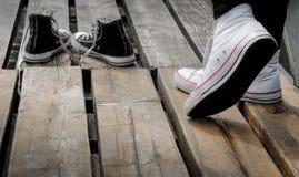 Chaussures blanches de port d'adolescent se tenant derrière les ricanements noirs, concept bien choisi Photo stock