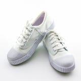 Chaussures blanches de sport sur le fond blanc Photo stock