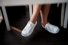 Chaussures blanches, jambes du ` s de femme de mode avec des espadrilles posées sur en bois Photo stock