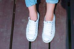 Chaussures blanches, jambes du ` s de femme de mode avec des espadrilles posées sur le plancher en bois Photographie stock
