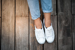 Chaussures blanches, jambes du ` s de femme de mode avec des espadrilles posées sur le plancher en bois Photos libres de droits