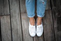 Chaussures blanches, jambes du ` s de femme de mode avec des espadrilles posées sur le plancher en bois Photo libre de droits
