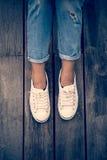 Chaussures blanches, jambes du ` s de femme de mode avec des espadrilles posées sur le plancher en bois Image stock