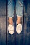 Chaussures blanches, jambes du ` s de femme de mode avec des espadrilles posées sur le plancher en bois Photo stock
