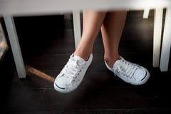 Chaussures blanches, jambes du ` s de femme de mode avec des espadrilles posées sur le plancher en bois Images stock