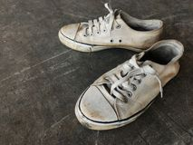 Chaussures blanches sales et vieilles sur l'au sol sale de ciment Photographie stock